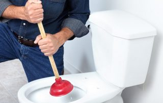 A clogged toilet being plunged