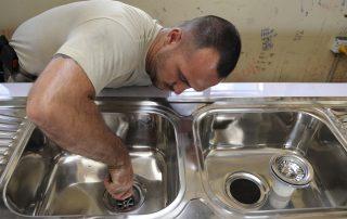 A plumber fixing a sink drain